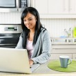 Woman using computer in kitchen — Stockfoto #6651350