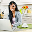 Woman using computer in kitchen — Stockfoto