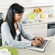 Stock Photo: Young womusing computer in kitchen