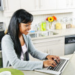 图库照片: Young woman using computer in kitchen