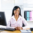 Smiling black businesswoman at desk - Stockfoto