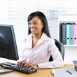 Smiling black businesswoman at desk — Stock Photo #6651519