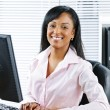 Royalty-Free Stock Photo: Happy black businesswoman at desk
