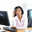 Worried black businesswoman at desk - Stock Photo