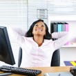 Black businesswoman resting at desk - Stock Photo