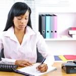 Serious black businesswoman at desk — Stock Photo