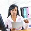 Black businesswoman working at desk - Stock Photo