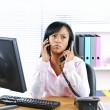 Stock Photo: Black businesswoman using two phones at desk