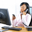 Royalty-Free Stock Photo: Black businesswoman using two phones at desk