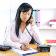 Serious black businesswoman on phone at desk — Stock Photo