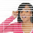 Woman looking through venetian blinds - Стоковая фотография