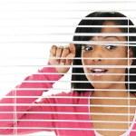 donna guardando attraverso tende veneziane — Foto Stock
