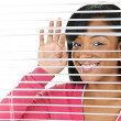 Smiling woman looking through blinds — Stock Photo #6651858