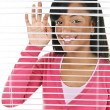 Smiling woman looking through blinds — Stock Photo