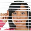 Woman looking through venetian blinds — Stock Photo