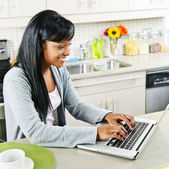 Young woman using computer in kitchen — Stock Photo