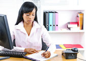 Serious black businesswoman at desk — Stock Photo