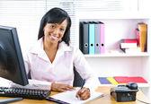 Улыбаясь черный предприниматель на стол — Стоковое фото