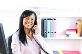 Smiling black businesswoman on phone at desk — Stock Photo