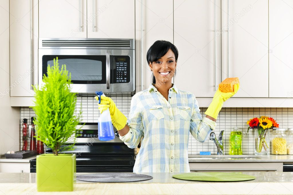 Smiling young black woman with sponge and rubber gloves cleaning kitchen  Stock Photo #6650985