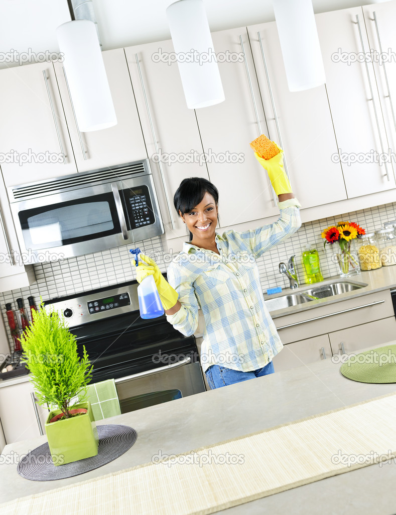 Young woman cleaning kitchen — Stock © elenathewise