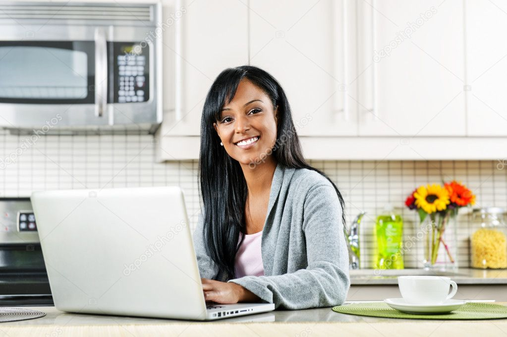 Smiling black woman using computer in modern kitchen interior — Stock Photo #6651375