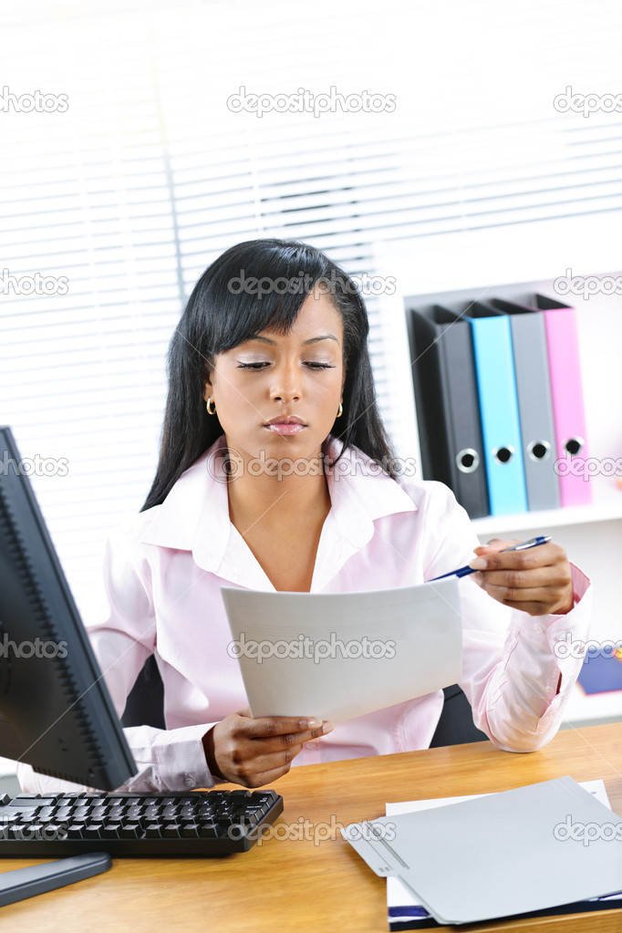 Young black business woman reading document at desk in office  Stock Photo #6651661