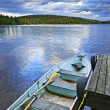 Rowboat docked on lake - Stock Photo