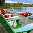 Deck chairs on dock at lake - Stock Photo