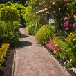Flower garden with paved path - Stock Photo