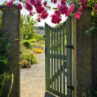 Open garden gate with roses - Stock Photo