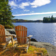 Adirondack chairs at lake shore — Stock Photo