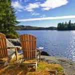 Adirondack chairs at lake shore — Stock Photo