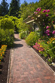 Flower garden with paved path — Stock Photo