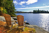 Adirondack chairs at lake shore — Stok fotoğraf