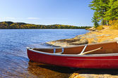 Red canoe on shore — Stock Photo