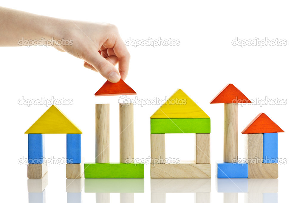 Hand building houses of wooden block toys isolated on white background  Stock Photo #6696469
