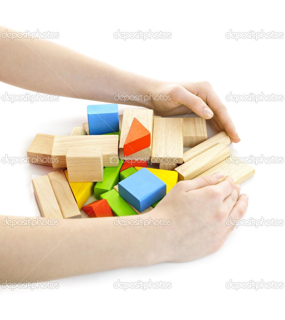 Hands gathering pile of wooden block toys isolated on white — Stock Photo #6696486