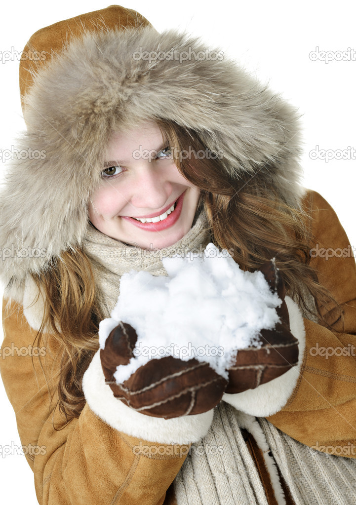 Playful young woman in winter coat with fur hood holding pile of fresh snow  Stock Photo #6697140