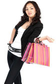 Asiatic young women in black jacket with shopping bags, isolated — Stock Photo