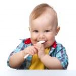 Cute little boy is biting spoon — Stock Photo #5414417