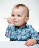 Cute little boy is biting spoon — Stock Photo