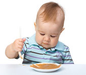 Cute little boy is playing with fruit puree — Stock Photo