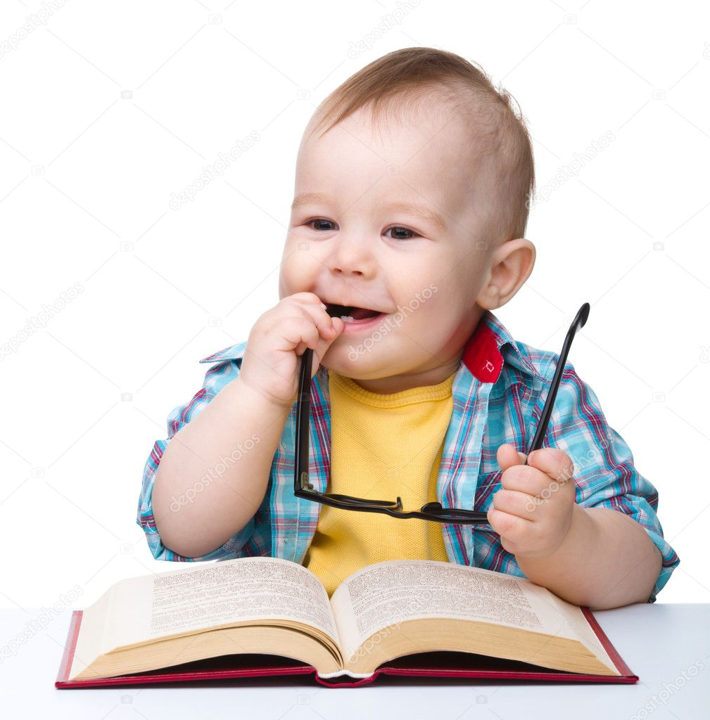 Cute little child play with book and glasses while sitting at table, isolated over white — Stock Photo #5414432