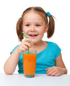 Happy little girl with orange juice — Stock Photo