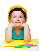 Cute little girl is playing while wearing hard hat — Stock Photo