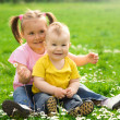 Two children are sitting on green meadow - Stock Photo