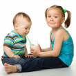 Sister is feeding her little brother — Stock Photo #5575305