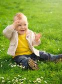 Little boy is sitting on green meadow — Stock Photo