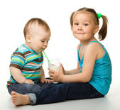 Sister is feeding her little brother — Stock Photo